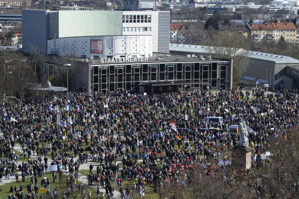 "Participants stand in front of the State Theater during a rally taking place under the motto ""Free citizens Kassel - basic rights and democracy"" in Kassel, Germany, Saturday, March 20, 2021. According to police, several thousand people were on the move in the city center and disregarded the instructions of the authorities during the unregistered demonstration against Corona measures. (Swen Pfoertner/dpa via AP)"