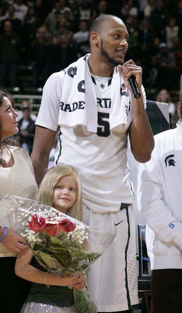 Michigan State senior Adreian Payne addresses the crowd during a senior day ceremony as he stands with his guest, Lacey Holsworth, an 8-year-old from St. Johns, Mich., who is battling cancer, following an NCAA college basketball game against Iowa, Thursday, March 6, 2014, in East Lansing, Mich. Michigan State won 86-76. (AP Photo/Al Goldis)