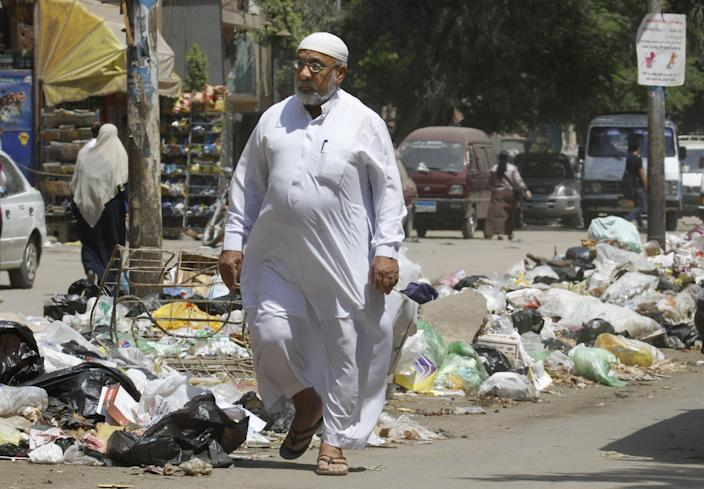 ADVANCE FOR SUNDAY, SEPT. 2 - In this Thursday, Aug. 16, 2012 photo, an Egyptian walks in front of loads of garbage on a street in Cairo, Egypt. A government modernization effort flopped. A swine flu panic prompted the mass slaughter of the pigs that recycled Cairo's organic garbage; the city's metal trash bins were easy prey for thieves, especially during the global scrap metal boom. Now the garbage crisis in the Arab world's biggest city is posing a significant test for the newly elected government that replaced longtime autocratic leaders. (AP Photo)