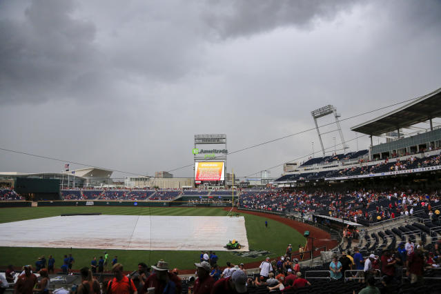 Clouds hang over TD Ameritrade Park as the threat of thunderstorms causes a weather delay in the sixth inning of an NCAA College World Series baseball game between Texas and Arkansas, in Omaha, Neb., Sunday, June 17, 2018. (AP Photo/Nati Harnik)