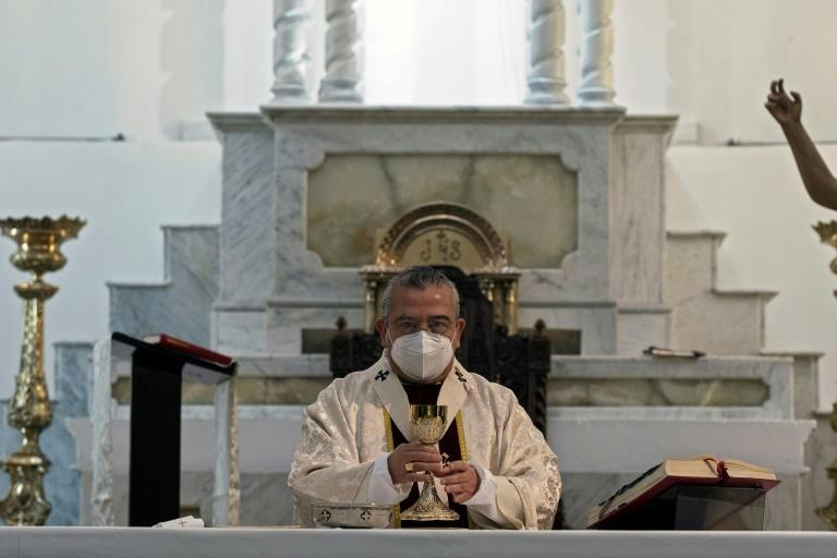 Mexican Archbishop Francisco Moreno Barron wears a face mask as he celebrates Easter Mass at the empty cathedral in Tijuana