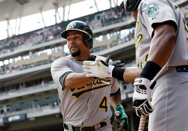 Oakland Athletics' Coco Crisp, left, is congratulated by Yoenis Cespedes after scoring on a single by Jed Lowrie off Minnesota Twins pitcher Scott Diamond in the third inning of a baseball game, Thursday, Sept. 12, 2013 in Minneapolis. (AP Photo/Jim Mone)