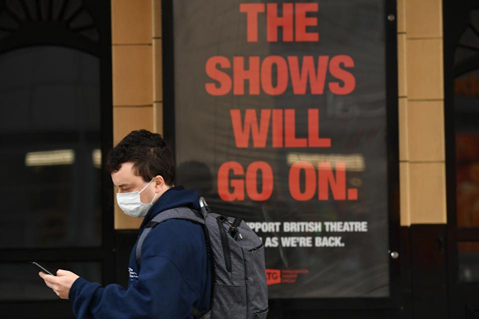 A person wearing a mask walks past a sign at the Palace Theatre in Manchester, as the Government is preparing to impose stringent new coronavirus controls on 2.8 million people after talks with the local leaders for Greater Manchester failed to reach agreement. Leaders have been given until midday on Tuesday to reach a deal, or face unilateral Government action, after 10 days of negotiations failed to reach an agreement.