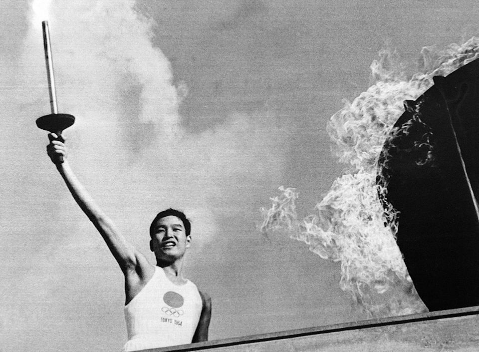 <p>Japanese Olympic torch runner Yoshinori Sakai lights the Olympic torch during the opening ceremony of the 1964 Tokyo Olympic Games. </p>