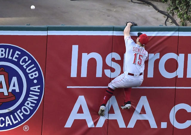 Cincinnati Reds third baseman Nick Senzel can't reach a ball hit for a solo home run by Los Angeles Angels' Justin Bour during the fifth inning of a baseball game Wednesday, June 26, 2019, in Anaheim, Calif. (AP Photo/Mark J. Terrill)