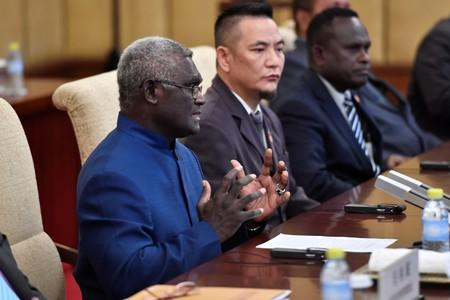 Solomon Islands Prime Minister Manasseh Sogavare talks to Chinese President Xi Jinping during their meeting at the Diaoyutai State Guesthouse in Beijing