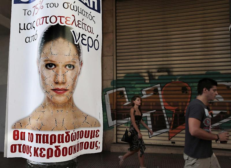 """People walk past a poster against the planned privatization of Greece's state-run water utilities, in central Athens, on Thursday Sept. 12, 2013. The writing on the poster reads """"Water makes up 75 percent of the human body. Do you want to hand it to profiteers?"""" Greece's conservative-led government is planning to privatize the country's two largest water companies and overhaul the regulatory framework in a process due to be completed next year as part of a massive state privatization drive being carried out as part of its bailout commitments. (AP Photo/Dimitri Messinis)"""