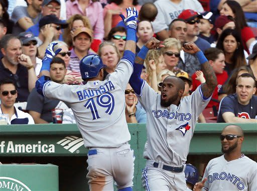 Toronto Blue Jays' Jose Bautista (19) celebrates his solo home run with teammate Jose Reyes, second from right, in the sixth inning of a baseball game against the Boston Red Sox in Boston, Saturday, June 29, 2013. (AP Photo/Michael Dwyer)