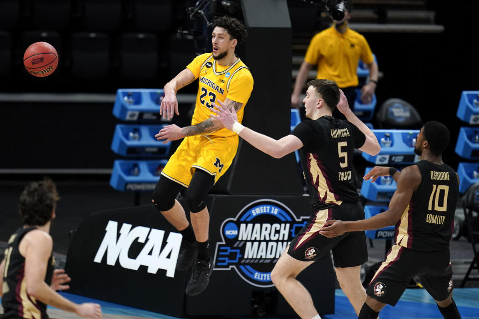 Michigan forward Brandon Johns Jr. (23) passes ahead of Florida State center Balsa Koprivica (5) and forward Malik Osborne (10) during the second half of a Sweet 16 game in the NCAA men's college basketball tournament at Bankers Life Fieldhouse, Sunday, March 28, 2021, in Indianapolis. (AP Photo/Jeff Roberson)