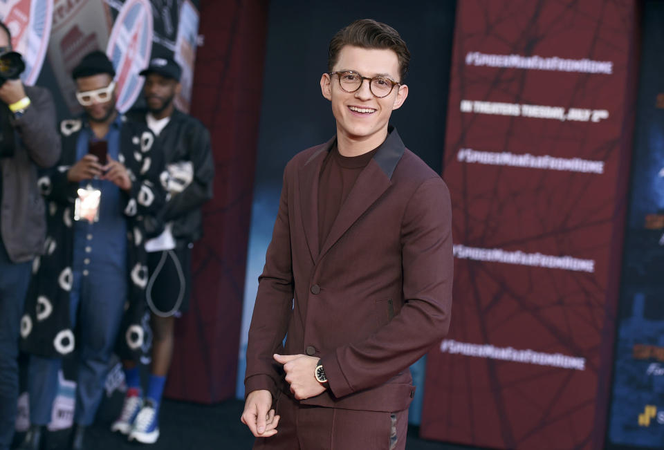 """FILE - In this June 26, 2019 file photo, Tom Holland arrives at the world premiere of """"Spider-Man: Far From Home"""" in Los Angeles. Hollywood studios are shuffling more release dates as a result of the coronavirus, including """"Doctor Strange 2"""" and the sequels to """"Spider-Man: Far From Home"""" and """"Into the Spider-Verse."""" Late Friday, both Sony Pictures and The Walt Disney Co. announced updated theatrical release schedules including some significant delays to some of their marquee superhero films. Sony's live-action Spider-Man has been pushed back to November 2021. (Photo by Jordan Strauss/Invision/AP, File)"""