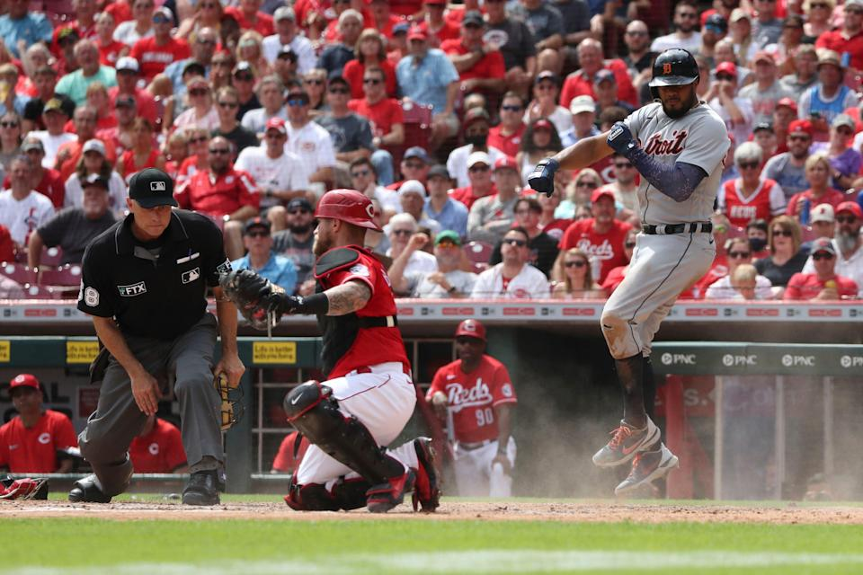 Detroit Tigers' Jeimer Candelario, right, leaps in the air after scoring on a sacrifice fly off the bat of Eric Haase, as Cincinnati Reds catcher Tucker Barnhart, center, looks for the call from home plate umpire Dan Iassogna during the sixth inning of a baseball game, Sunday, Sept. 5, 2021, in Cincinnati.
