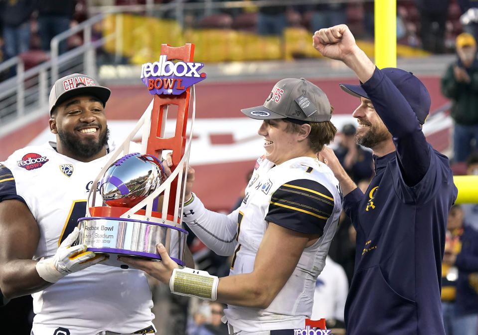California defensive end Zeandae Johnson, left, quarterback Chase Garbers (7) and head coach Justin Wilcox, right, celebrate with the trophy after a win over Illinois in the Redbox Bowl NCAA college football game Monday, Dec. 30, 2019, in Santa Clara, Calif. (AP Photo/Tony Avelar)
