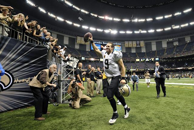 New Orleans Saints quarterback Drew Brees (9) responds to the crowd as he walks off the field after an NFL football game against the Miami Dolphins in New Orleans, Monday, Sept. 30, 2013. The Saints won 38-17. (AP Photo/Bill Feig)