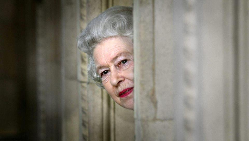 <p>Queen Elizabeth II peers round a corner during a visit to the Royal Albert Hall in London, following the end of an eight-year restoration program. (PA Archive) </p>
