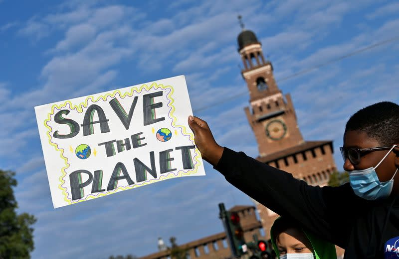 FILE PHOTO: A demonstrator holds up a sign as he attends a Fridays for Future climate strike in Milan, Italy ahead of Glasgow's COP26 meeting