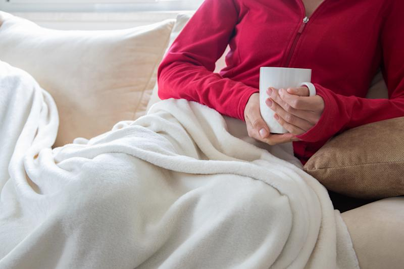 Crop view of young adult woman is relaxing on comfortable sofa with hot beverage. Cozy lazy time indoor. Cold seasons - cold and flu