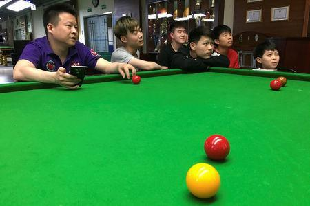 Students watch live Ding Junhui playing against Mark Selby on the television during the Betfred World Snooker Championship, at World Snooker College in Beijing, China, April 28, 2017. Picture taken April 28, 2017. REUTERS/Thomas Suen