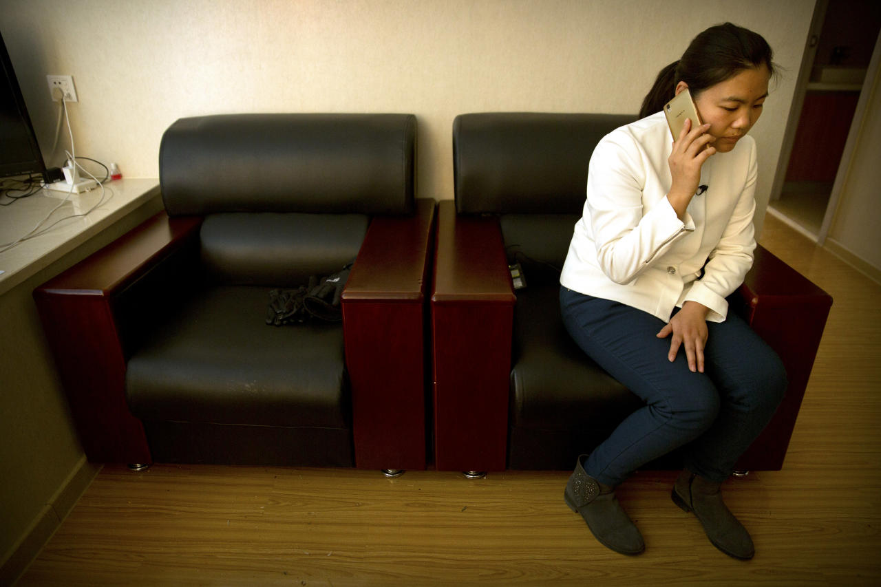 Xu Yan, the wife of Chinese lawyer Yu Wensheng, talks on her cellphone in their apartment on the outskirts of Beijing, Friday, Jan. 19, 2018. The wife of a Chinese human rights lawyer says her husband was taken into police custody Friday morning while taking his son to school, a day after he posted a letter online calling on China's ruling communist party to reform the Chinese constitution and allow open presidential elections. (AP Photo/Mark Schiefelbein)