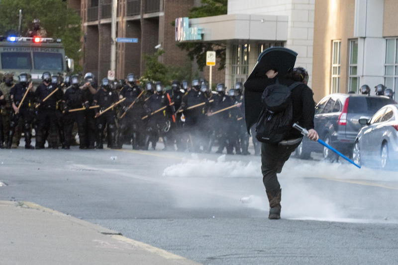 In this Monday, June 1, 2020 photo, a person kicks back a canister of tear gas while taking fire of rubber bullets after police used tear gas and rubber bullets against peaceful protesters before curfew in Pittsburgh, protesting the death of George Floyd, who died after being restrained by Minneapolis police officers on May 25. (Christian Snyder/Pittsburgh Post-Gazette via AP)