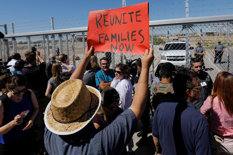 A protester holds up a sign as mayors from U.S. cities are stopped from entering the children's tent encampment in Tornillo, Texas, on June 21. (Mike Blake / Reuters)