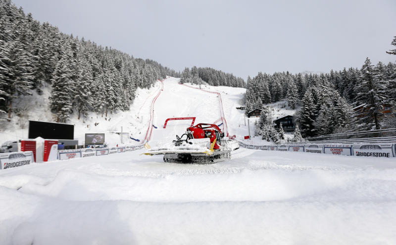 A snow plough at work as fresh snow in conjunction with the too soft base in the lower section of the course forced the jury to cancel a training for the women's alpine skiing World Cup downhill race in Crans-Montana, Switzerland, Friday, Feb. 28, 2014. (AP Photo/Marco Trovati)