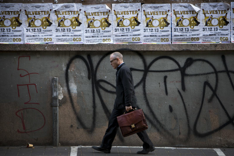 A man walks past posters advertising a New Years Eve party in Tel Aviv, Israel, Monday, Dec. 30, 2013. In Israel, the somber, soul-searching and autumnal new year of the lunar Jewish calendar overshadows the Gregorian's Jan. 1. (AP Photo/Oded Balilty)