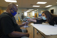 Emily Smith tests Larry Brown's hand strength during an occupational therapy session at Community Health Network, Thursday, Aug. 20, 2020, in Indianapolis. His hands _ which helped make him Indiana State's eighth all-time receiving leader _ can't even open a can of soda. (AP Photo/Darron Cummings)