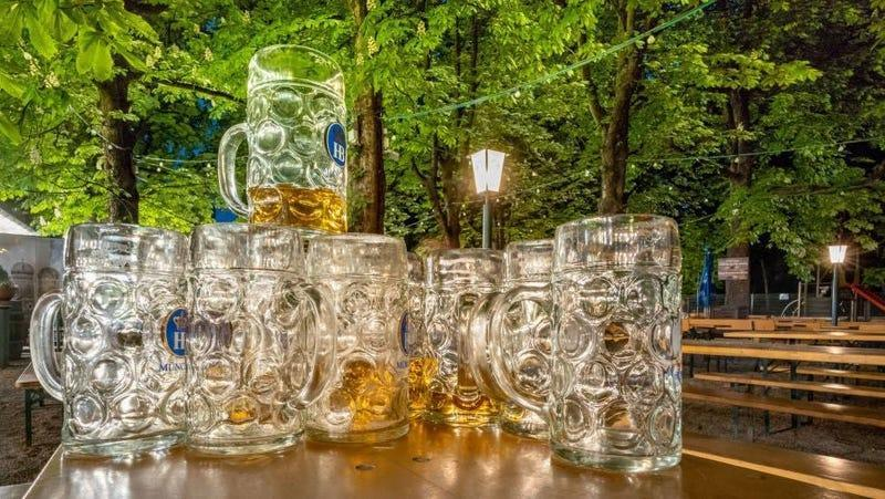 Stack of nearly empty beer steins in leafy beer garden