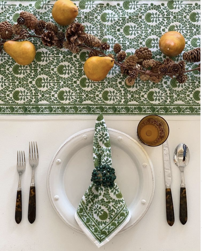 """<p><a href=""""https://pomegranateinc.com/"""" rel=""""nofollow noopener"""" target=""""_blank"""" data-ylk=""""slk:Pomegranate"""" class=""""link rapid-noclick-resp"""">Pomegranate</a> creatively uses pinecones and golden pears to create a sophisticated garland that really stands out against the green table runner.</p>"""