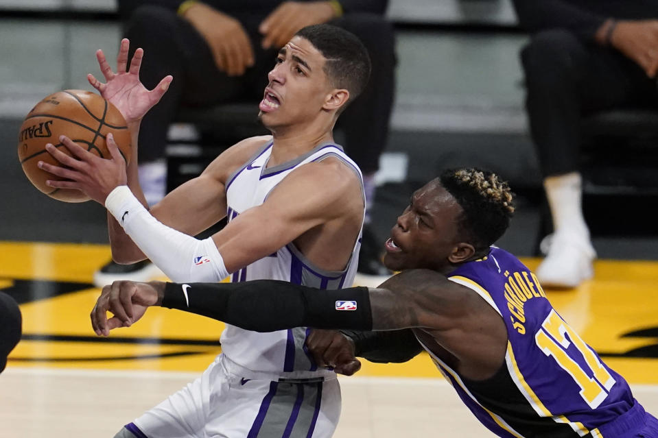 Sacramento Kings guard Tyrese Haliburton, left, drives past Los Angeles Lakers guard Dennis Schroeder (17) during the second half of an NBA basketball game Friday, April 30, 2021, in Los Angeles. (AP Photo/Marcio Jose Sanchez)