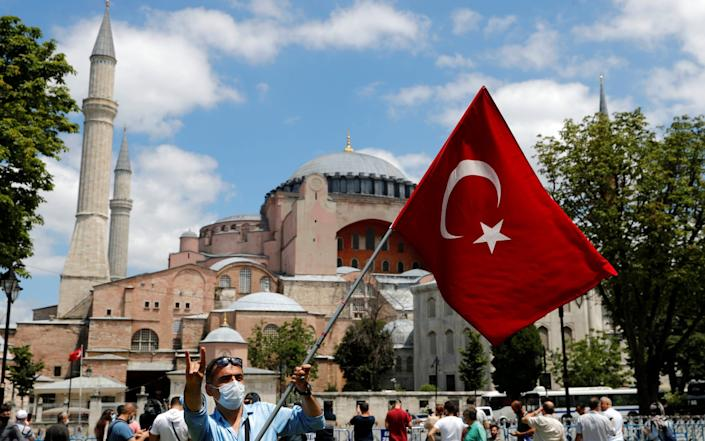 A man waves a Turkish flag in front of the Hagia Sophia - Murad Sezer /Reuters