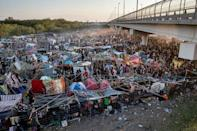 PHOTO: Migrants take shelter along the Del Rio International Bridge at sunset as they await to be processed after crossing the Rio Grande river into the U.S. from Ciudad Acuna in Del Rio, Texas, Sept. 19, 2021. (Adrees Latif/Reuters, FILE)