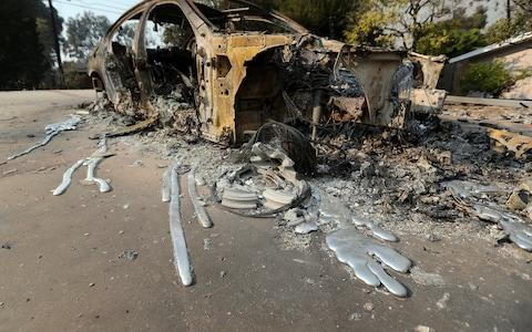 Molten aluminum has flowed from a car that burned in front of one of at least 20 homes destroyed just on Windermere Drive in the Point Dume area of Malibu, Calif. - Credit: AP