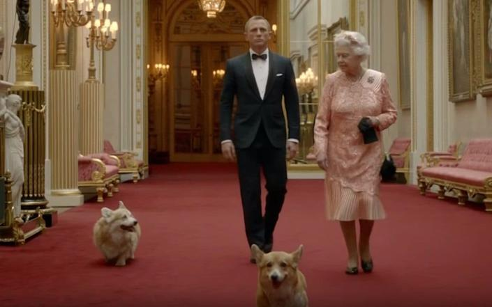 Daniel Craig and Queen Elizabeth II with two corgis and a footman during the film shown as part of the London 2012 Olympic Games opening ceremony.