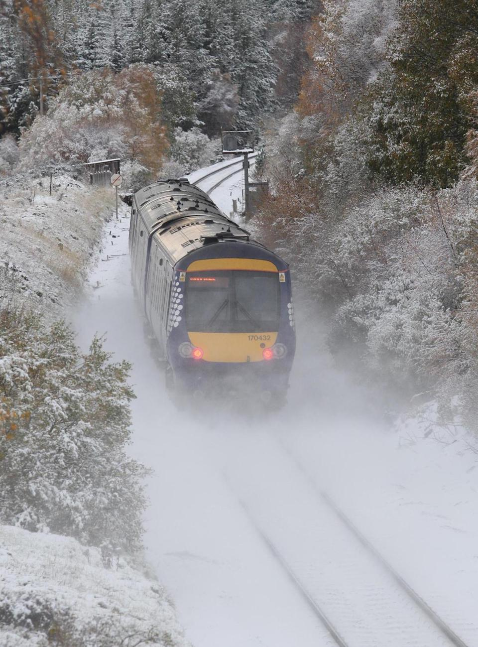 <p>A train makes its way through a dusting of snow in Inverness </p>