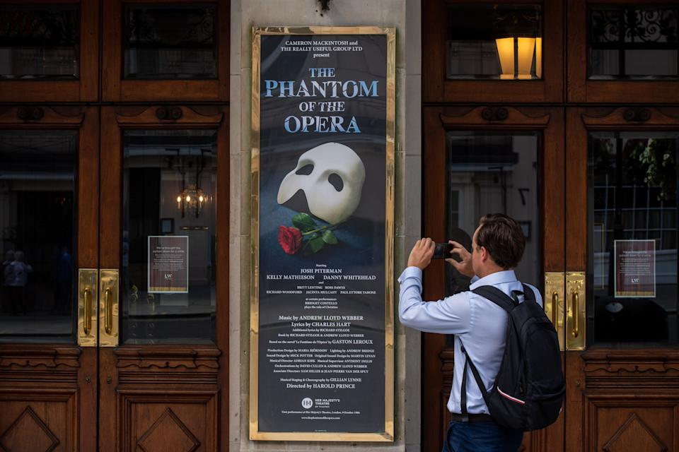 LONDON, ENGLAND - JULY 29: A man takes photographs of signs at Her Majestys Theatre, home to Phantom of the Opera, on July 29, 2020 in London, England. Phantom of the Opera, London's second-longest-running musical, has been forced to close permanently on the West End, the show's producer has announced. The show, which has been running at Her Majesty's Theatre since 1986, will no longer operate in the West End, due to the financial impacts of the ongoing coronavirus restrictions on theatres. (Photo by Chris J Ratcliffe/Getty Images)