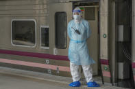 A health worker wearing protective gear stands outside a train at Rangsit train station in Pathum Thani Province, Thailand while a COVID-19 patient prepares inside the train to head to her hometown Tuesday, July 27, 2021. Thai authorities began transporting some people who have tested positive with the coronavirus from Bangkok to their hometowns on Tuesday for isolation and treatment, to alleviate the burden on the capital's overwhelmed medical system. (AP Photo/Sakchai Lalit)