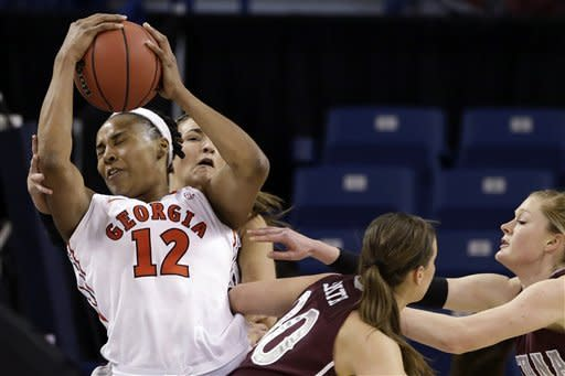 Georgia's Jasmine Hassell (12) struggles to control the ball while surrounded by Montana players in the first half during a first-round game in the women's NCAA college basketball tournament in Spokane, Wash., Saturday, March 23, 2013. (AP Photo/Elaine Thompson)