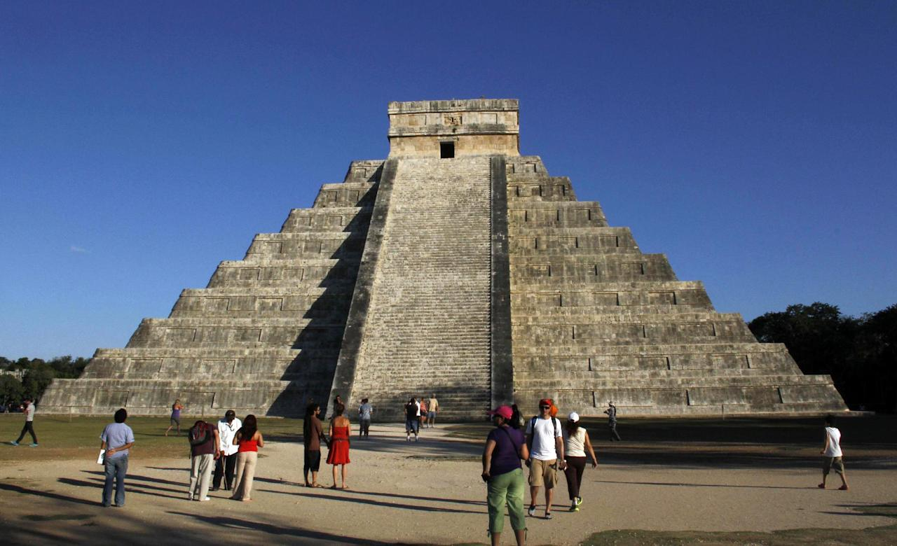 People gather in front of the Kukulkan Pyramid in Chichen Itza, Mexico, Thursday, Dec. 20, 2012. American seer Star Johnsen-Moser led a whooping, dancing, drum-beating ceremony Thursday in the heart of Mayan territory to consult several of the life-sized crystal skulls, which adherents claim were passed down by the ancient Maya. (AP Photo/Israel Leal)