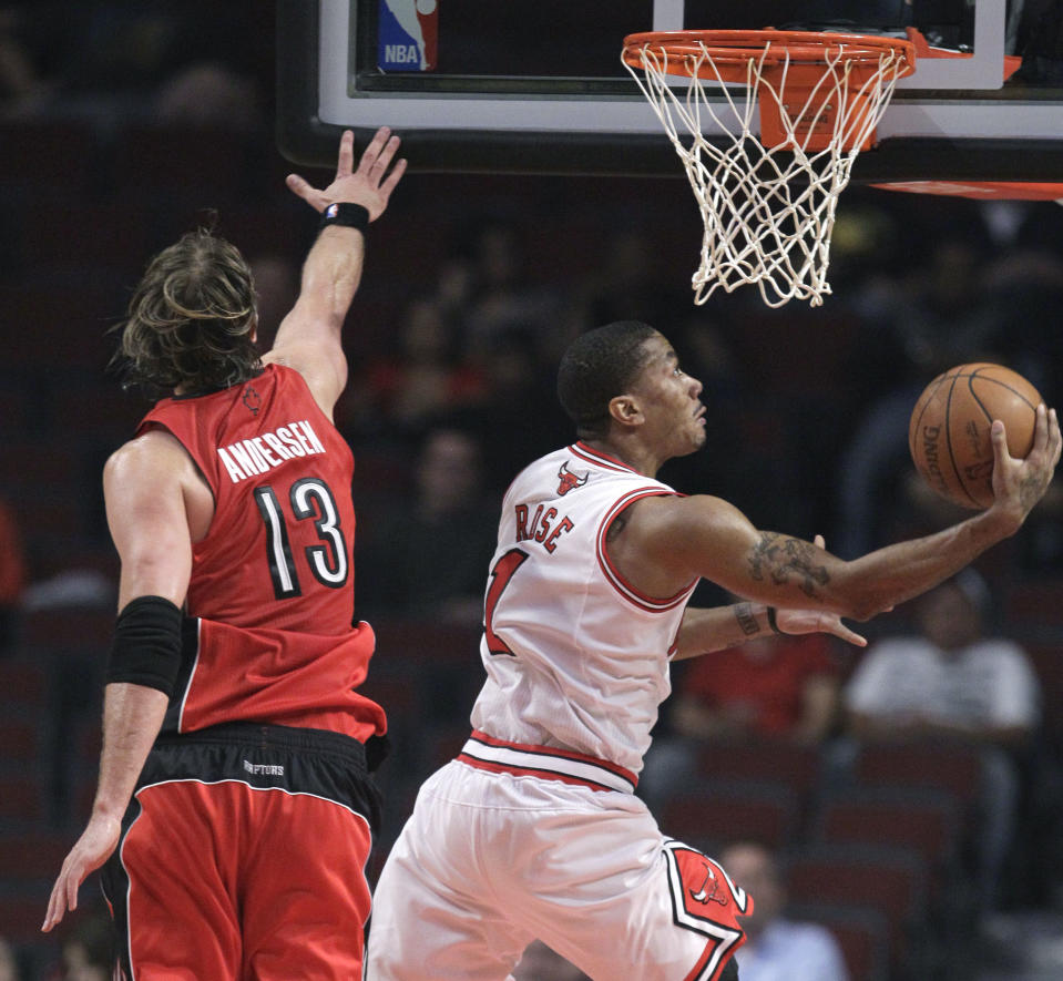 Chicago Bulls point guard Derrick Rose shoots a reverse layup past Toronto Raptors center David Andersen during the first quarter of an NBA basketball preseason game Tuesday, Oct. 12, 2010, in Chicago.