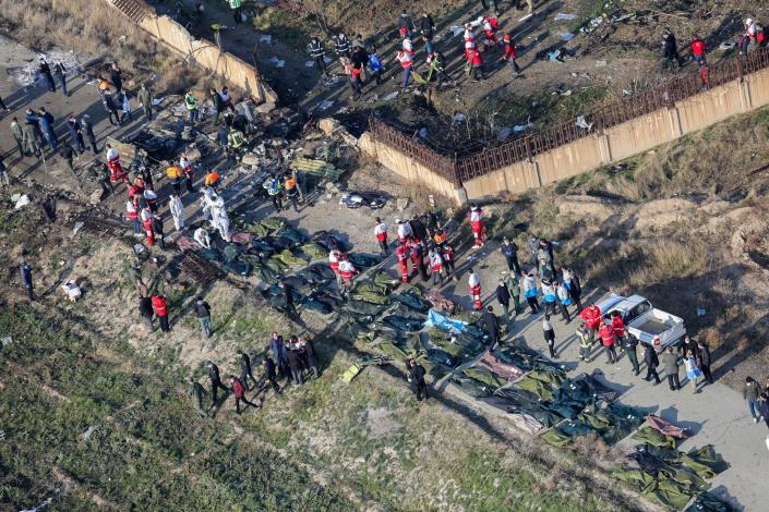 People and rescue teams are pictured amid bodies and debris after a Ukrainian plane carrying 176 passengers crashed near Imam Khomeini airport in the Iranian capital Tehran early in the morning on January 8, 2020, killing everyone on board. (Photo by Rouhollah Vahdati/ISNA/AFP via Getty Images)