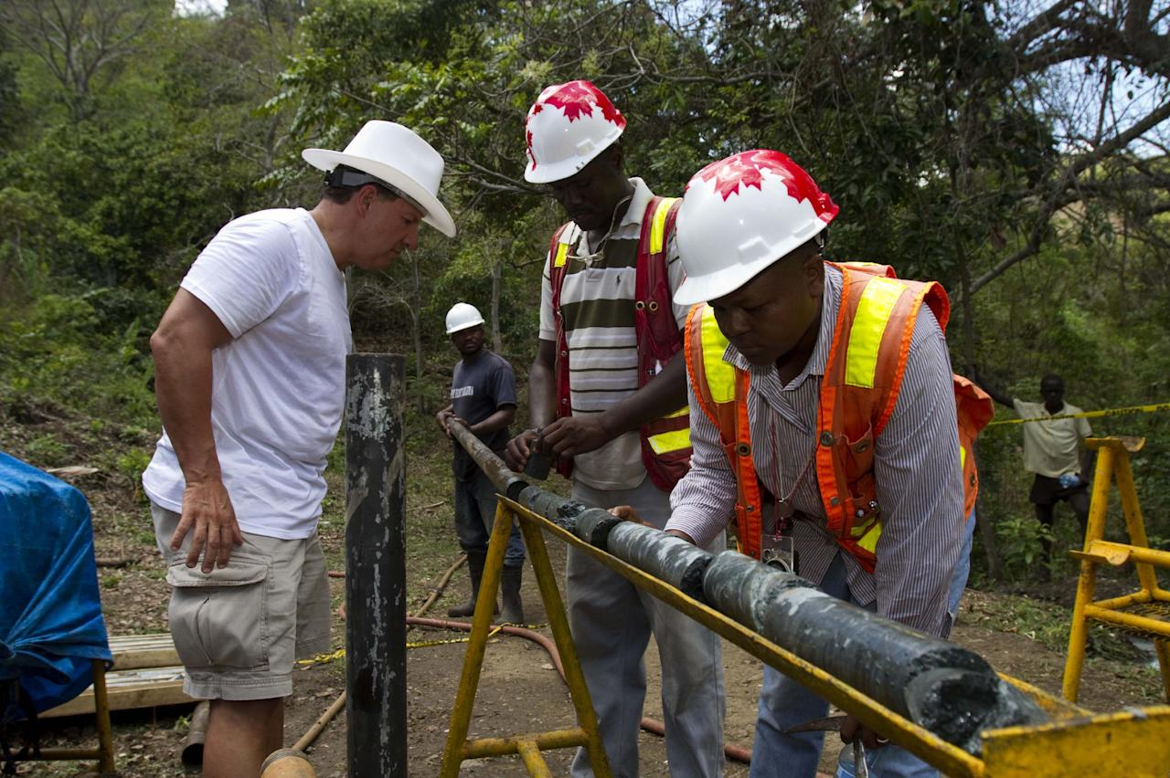 In this April 10, 2012 photo, Daniel Hachey, president resources MAJESCOR, left, and geologist Francisque Pierre, right, examine samples of stone for minerals and metals at a drill site in the department of Trou Du Nord, Haiti. Haiti's land may yet hold the solution to centuries of poverty: there is gold hidden in its hills, and silver and copper too. Now, two mining companies are drilling around the clock to determine how to get those metals out, and how much it might cost. (AP Photo/Dieu Nalio Chery)