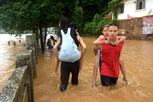<p>People wade in a flooded street on July 2, 2017 in Yongfu, China. Heavy rainstorms hit south China since late June and caused severe floods in many parts of Hunan, Guangxi, Jiangxi and Sichuan. (Photo: VCG/VCG via Getty Images) </p>