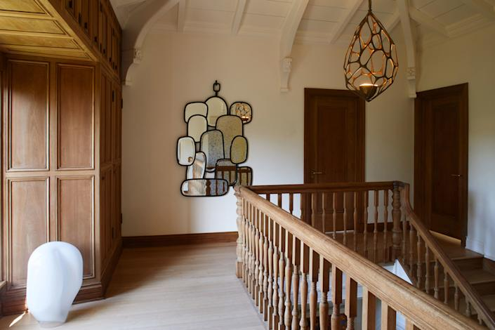 "<div class=""caption""> A Hubert Le Gall mirror reflects the light at the top of the stairway, and a <a href=""http://www.vanderstraeten.fr/en/"" rel=""nofollow noopener"" target=""_blank"" data-ylk=""slk:Herve Van der Straeten"" class=""link rapid-noclick-resp"">Herve Van der Straeten</a> chandelier overlooks the scene. </div>"
