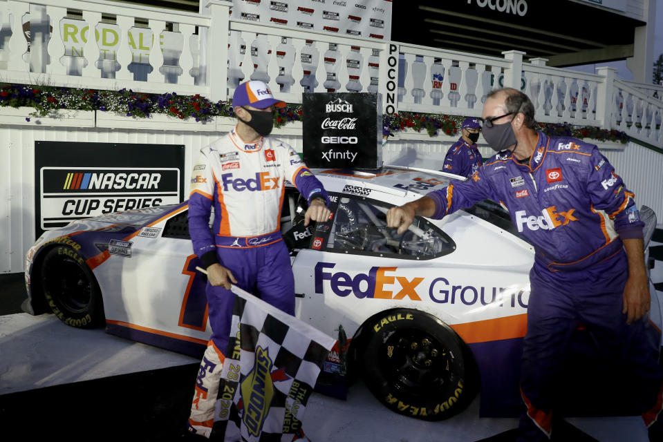 Denny Hamlin, left, celebrates with a team member after winning the NASCAR Cup Series auto race at Pocono Raceway, Sunday, June 28, 2020, in Long Pond, Pa. (AP Photo/Matt Slocum)