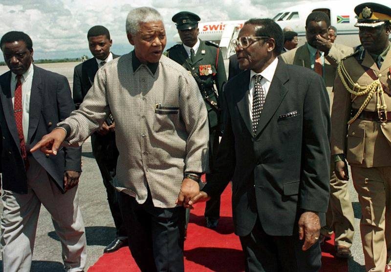 FILE - This Sunday Dec. 13, 1998 file photo shows former South African president Nelson Mandela, left, with Zimbabwean President Robert Mugabe in Harare. Mandela, now in a hospital, quit after a single term as South African president. Robert Mugabe, Africa's oldest head of state, is still in charge of Zimbabwe after disputed elections last week. These two larger-than-life figures, who chose different paths once in power, represent a rivalry over style and ideas that resonates beyond southern Africa. (AP Photo/Rob Cooper, File)