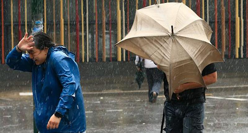 People battling wild weather with umbrellas as heavy rain falls in Sydney.