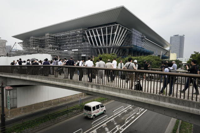 FILE - In this July 3, 2019, file photo, members of the media gather outside the Tokyo Aquatics Center, a venue for swimming and diving at the Tokyo 2020 Summer Olympics in Tokyo. The Olympics will be simply a sideshow for some Tokyo visitors, astounded by the cleanliness, courtesy and order. Japans sprawling capital is a dense mix of the traditional and eccentric where bowing meets bustle. (AP Photo/Jae C. Hong, File)
