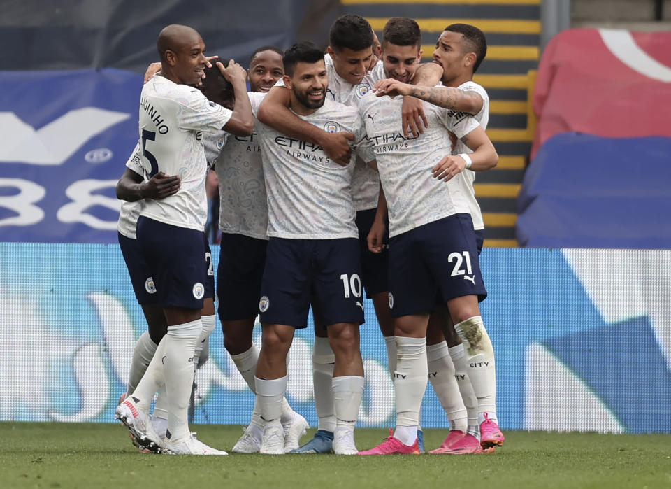 Manchester City's Sergio Aguero, centre, is congratulated by teammates after scoring his team's first goal during the English Premier League soccer match between Crystal Palace and Manchester City at Selhurst Park in London, England, Saturday, May 1, 2021. (AP Photo/Clive Rose/Pool)