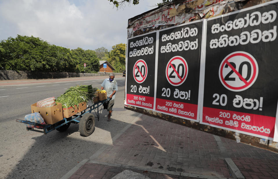 "A Sri Lankan vegetable seller pushes his cart past posters against a proposed constitutional amendment that would consolidate power in the president's hands in Colombo, Sri Lanka, Tuesday, Oct. 20, 2020. Sinhalese reads "" No to 20 even with amendments"". (AP Photo/Eranga Jayawardena)"